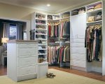 Built in closet with cabinet, drawers, shoe storage and island and dressing seat